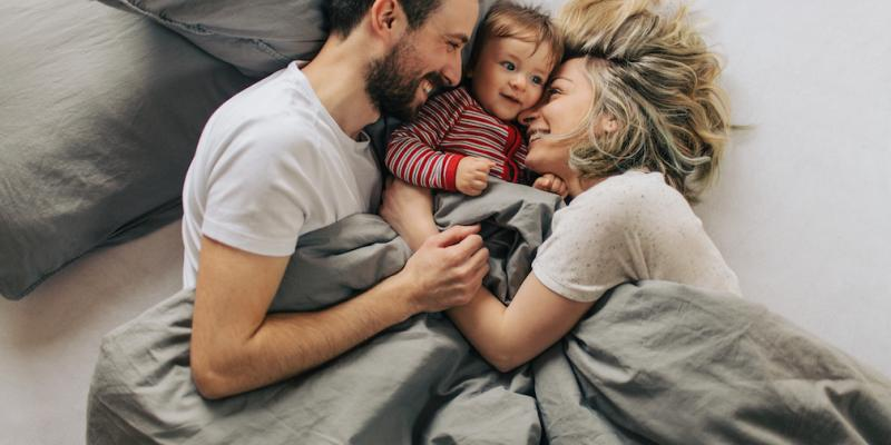 Mom, dad, and toddler snuggling in a bed that is free of bed bugs thanks to B&T's bed bug control service.
